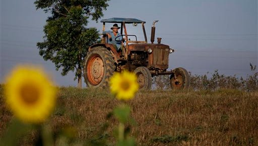 In this Feb. 22, 2011 file photo, a farmer drives his tractor in Pinar del Rio, Cuba. The Obama administration has approved the first U.S. factory in Cuba in more than half a century, allowing a pair of former software engineers to build a plant assembling as many as 1,000 small tractors a year. The partners were notified by Treasury Department officials in February 2016.