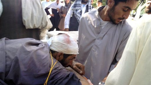 A man who was injured in a suicide bombing is helped at the main hospital in Sharan, Afghanistan.