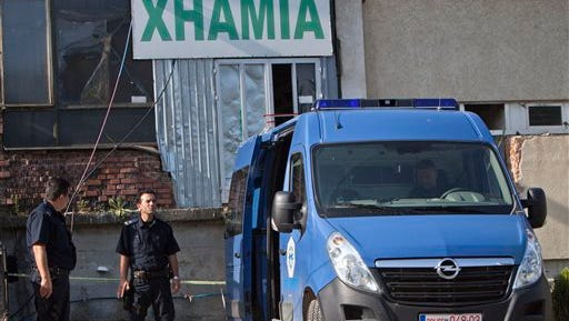 """Kosovo police officers guard the entrance of a makeshift mosque after a raid in Kosovo's capital Pristina, Monday, Aug. 11, 2014. Kosovo police arrested at least 40 people in a major operation targeting Islamic radicals suspected of fighting alongside extremists in Iraq and Syria. Weapons, ammunition and explosives were seized early Monday as hundreds of police officers and special police units raided 60 locations across Kosovo, including makeshift mosques believed to have served as recruiting centres. Sign in background """"Xhamia"""" in Albanian is for mosque. (AP Photo/Visar Kryeziu)"""