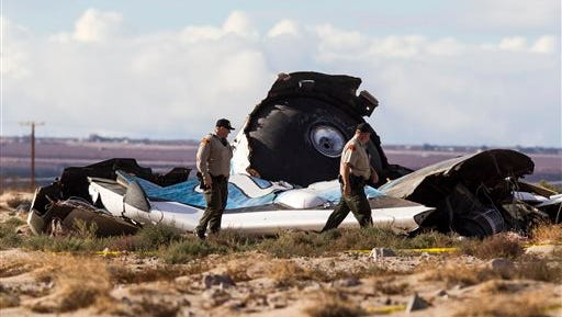 Law enforcement officials take a closer look at the wreckage near the site where a Virgin Galactic space tourism rocket, SpaceShipTwo, exploded and crashed in Mojave, Calif. Saturday, Nov 1, 2014. The explosion killed a pilot aboard and seriously injured another while scattering wreckage in Southern California's Mojave Desert, witnesses and officials said. (AP Photo/Ringo H.W. Chiu)