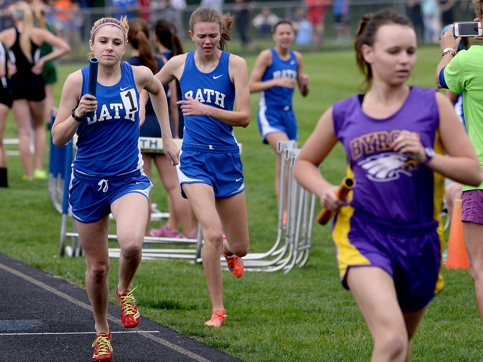 Bath's Kelsey Billingsley gets the baton from teammate Melissa Schott en route to a first place finish during the finals of the girls 4x800-meter relay Friday May 15, 2015, at the Division 3 Regional meet at Bath High School.