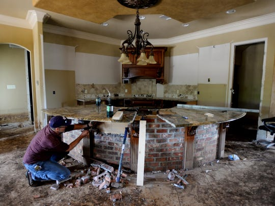 Jamie Sheppard of Sheppard's Countertops helps River Bluff homeowner Randy Wright remove his marble countertop Wednesday morning.