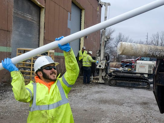 Rian Lopez from EnviroCore Inc carries a long pipe