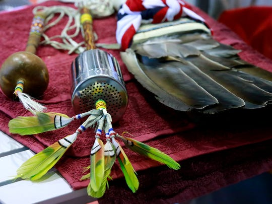 A natural gourd, an artificial gourd and eagle feathers belonging to Raymond Pete are displayed Saturday at the Aztec Boys & Girls Clubs gym.