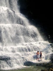 People cool off in the waterfall at Burgess Falls State