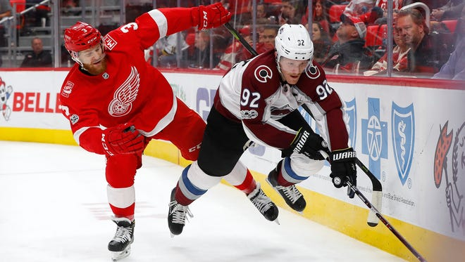 Detroit Red Wings defenseman Nick Jensen (3) and Colorado Avalanche left wing Gabriel Landeskog (92) battle for a loose puck in the second period.