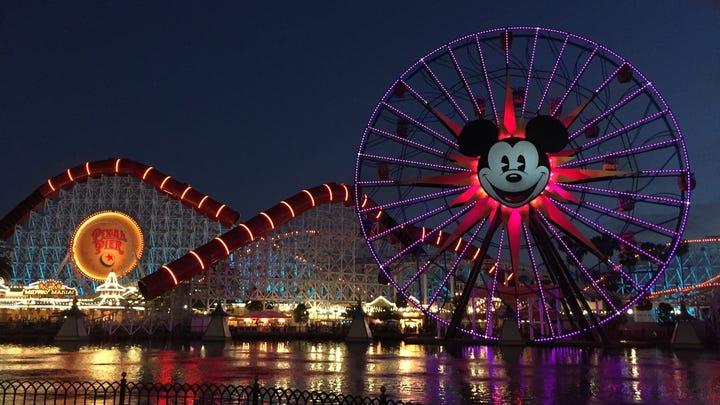 The Incredicoaster and Mickey's Fun Wheel at Disney California Adventure lit up at night.