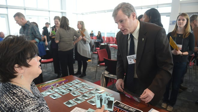"""York city mayor Michael Helfrich attempts to sell items to a """"pawn shop"""" during a poverty simulation sponsored by the Community Progress Council at York College on Thursday. A group of about 60 participants, made up of business and community leaders, went through 4 """"weeks"""" of living under the poverty line. The goal is to make them aware of the challenges facing York County residents who do live in poverty."""
