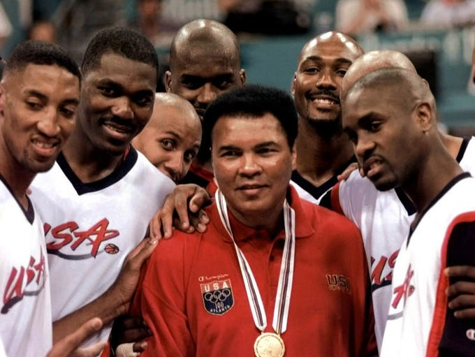 Muhammad Ali poses with Dream Team members from left: Scottie Pippen, Hakeem Olajuwon, Reggie Miller, Shaquille O'Neal, Karl Malone and Gary Payton after receiving the gold medal, which replaces the 1960 gold medal he lost, during halftime ceremonies at the gold medal game of basketball competition at the Centennial Summer Olympic Games in Atlanta Saturday, August 3, 1996.