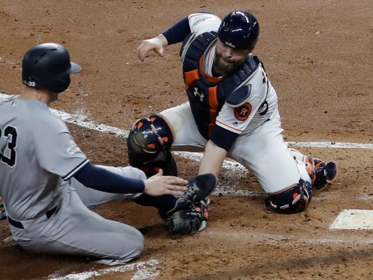 Houston Astros catcher Brian McCann tags out New York Yankees' Greg Bird at home during the fifth inning of Game 7 of baseball's American League Championship Series Saturday, Oct. 21, 2017, in Houston. (AP Photo/David J. Phillip)