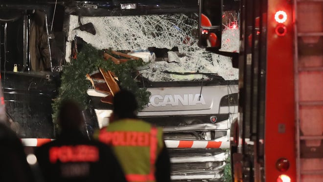 Police stand near a black lorry that ploughed through a Christmas market on Dec. 19, 2016 in Berlin.