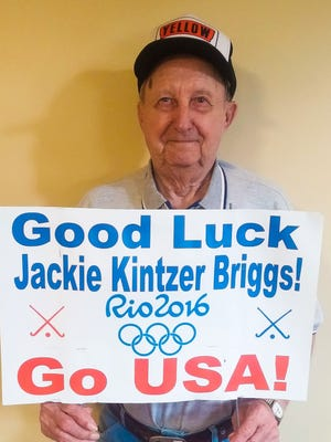 Paul Kintzer holds one of many signs that line Route 422 around the area of Conrad Weiser High School. Kintzer's granddaughter is a member of the U.S. women's field hockey team.