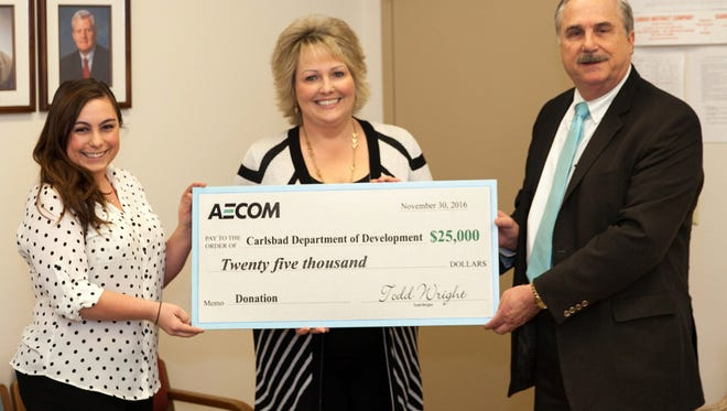 CDOD Local Development Coordinator Shannon Carr and CDOD executive committee vice president Susan Crockett accept a donation from Dr. Todd Wright of AECOM.
