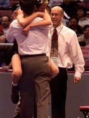 South Plainfield's Matt Anderson hugs South Plainfield head coach Bill Pavlak as assistant coach Kevin McCann pats him on the back moments after Anderson won the state final in the 103 wt. class, Saturday March 11, 2000.