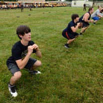 Cody Coakler does squats with the other four members of his group Thursday morning at Lancaster High School in Lancaster. Members of the Lancaster High School football team took part in the Marine Corps leadership training.