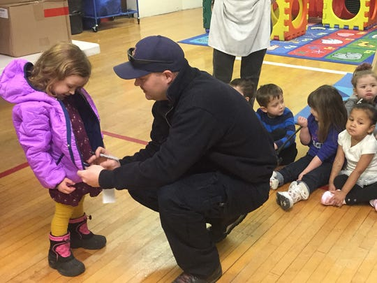 Ty Loney helps three-year-old Siobhan Riggins zip up her new jacket during the Operation Warm event at Head Start.