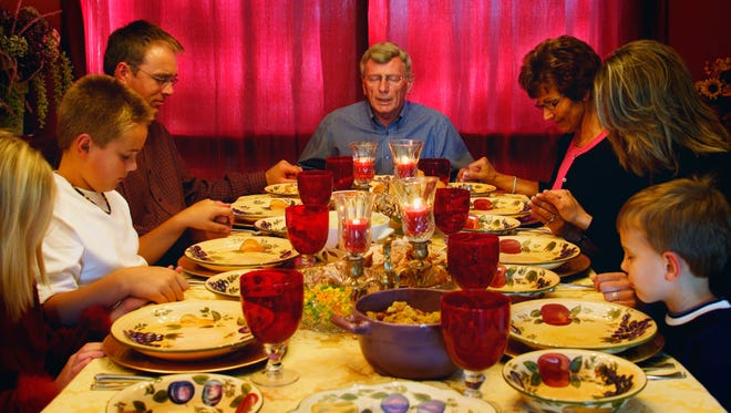 Family praying over meal.