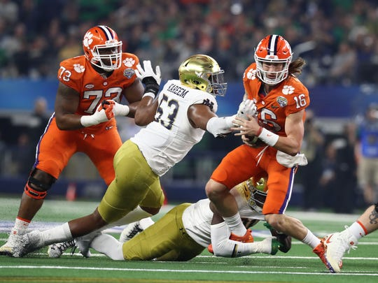 Dec 29, 2018; Arlington, TX, United States; Clemson Tigers quarterback Trevor Lawrence (16) tries to run away from Notre Dame Fighting Irish defensive lineman Khalid Kareem (53)  in the first half in the 2018 Cotton Bowl college football playoff semifinal game at AT&T Stadium. Mandatory Credit: Matthew Emmons-USA TODAY Sports