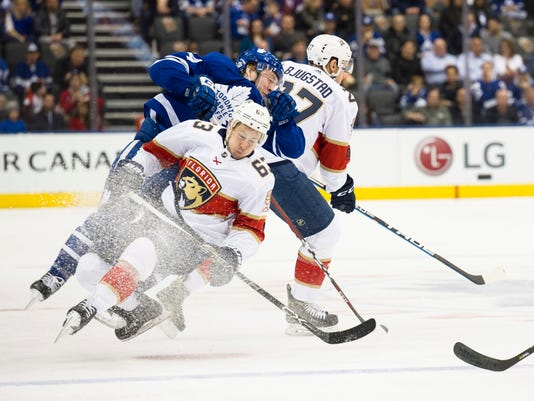 Toronto Maple Leafs defenseman Morgan Rielly (44) is checked by Florida Panthers center Nick Bjugstad (27) and Panthers right wing Evgenii Dadonov (63) during the first period of an NHL hockey game Tuesday, Feb. 20, 2018, in Toronto. (Christopher Katsarov/The Canadian Press via AP)