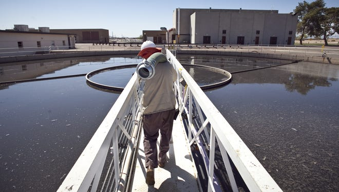 WATER RECYCLING: City worker Howard Hindman carries a hose so he can drain a primary clarifier for maintenance at the 91st Avenue Wastewater Treatment Plant in Phoenix. Five Valley cities signed a new agreement with the owners of the Palo Verde nuclear generating station for the use of billions of gallons of treated wastewater to cool the power plant. Another type of recycling -- home gray water filtration -- could help Arizonans with outdoor watering needs reduce their use of potable water.