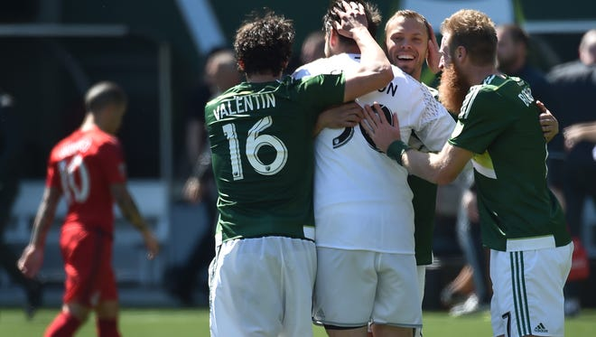 Portland Timbers goalkeeper Jake Gleeson is greeted by teammates after an MLS soccer game against Toronto FC in Portland, Ore., on Sunday, May 1, 2016. (AP Photo/Steve Dykes)