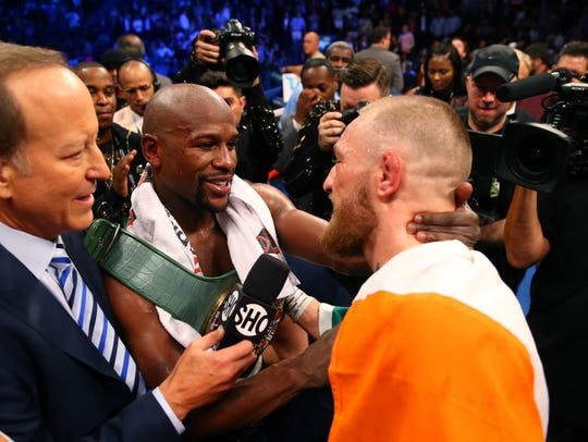 Floyd Mayweather Jr., left, embraces Conor McGregor,