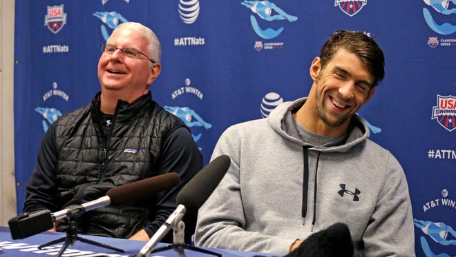 Michael Phelps, right, shares a laugh with his long-time coach Bob Bowman as they address media members at the U.S. Winter Nationals swimming event  Dec. 2, 2015, in Federal Way, Wash.