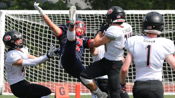 Eastchester High School's Drew Walpole is upended as Rye's Brendan Lavelle intercepts during their football against Rye, in Eastchester, Sept. 16, 2017.