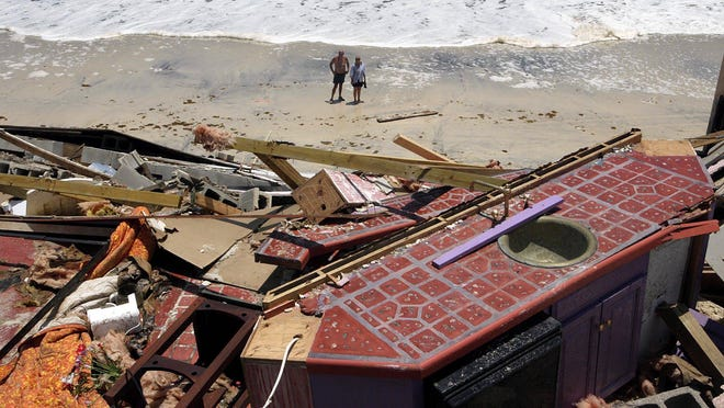Hurricane Dennis was an early season hurricane that made landfall near Pensacola on July 10, 2005 as a Category 3. In this photo Peggy Criser (right) and a friend look up at her $3 million waterfront home in Miramar Beach that was leveled by Hurricane Dennis.
