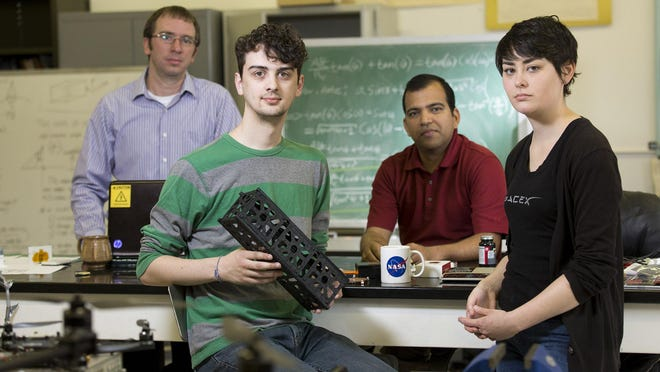 (L-R) Post Doc research scientist David Cotten of the Center for Geospatial Research, Senior computer science and astrophysics major Caleb Adams, Professor of Geography Deepak Mishra, and senior mechanical engineering major Megan Le Corre; are working together along with a team of students and professors in a collaborative effort to design, build, and deploy (with the help of NASA) a cube satellite. Adams is holding a 3D printer model of the CubeSat.