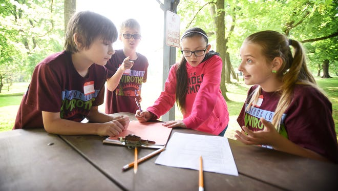 Working together in a group, fifth grade students from Jonestown Elementary School, from left, Lucas Novack, Kalib Sekellick, Savannah Hollinger and Reilly Harmon answer questions about nature while participating in Lebanon County's 23rd annual Elementary School Envirothon, held at Coleman Memorial Park in Lebanon on Thursday, May 12, 2016.  Palmyra's Pine Street Black team was named the winner of the envirothon, which is sponsored by the Lebanon County Conservation District. Team members are Maggie Copeland, Devon Grant, William Wolford, Julia Klucinec and Tyler Mahaffey.