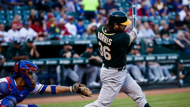 Oakland Athletics catcher Derek Norris follows through for a two-run RBI double against the Texas Rangers during the first inning at Rangers Ballpark in Arlington.