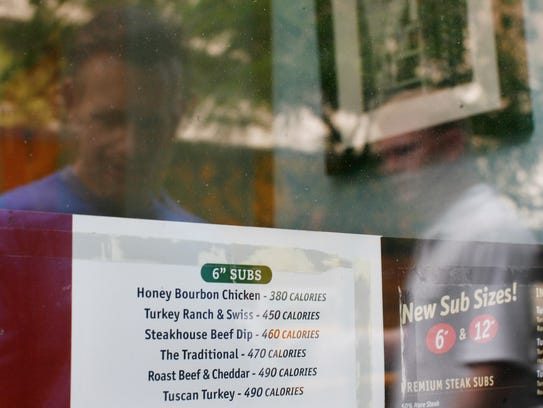 A restaurant window menu displays the calorie count