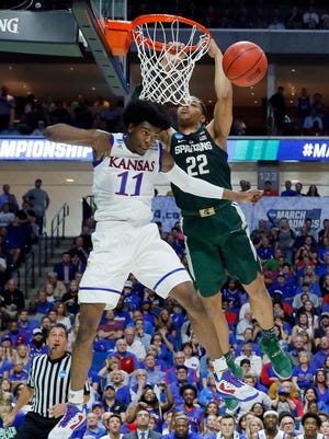Kansas guard Josh Jackson (11) breaks up a dunk attempt by Michigan State' Miles Bridges (22) in the first half of a second-round game in the men's NCAA college basketball tournament in Tulsa, Okla., Sunday, March 19, 2017. (AP Photo/Tony Gutierrez)