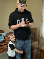 Josh Johnson's son, Connor, now 5, clings to his father's