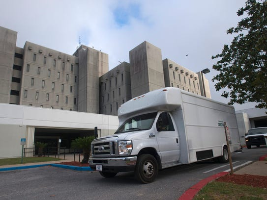 Escambia County Corrections transport vans leave the