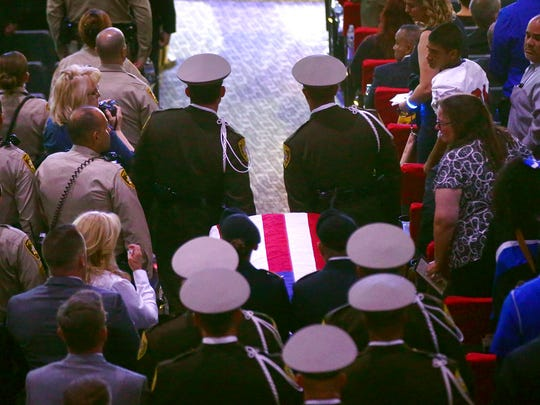 Pallbearers carry the casket of Las Vegas Police Officer