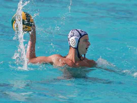 Drew Parsley of Redwood lines up a shot over Caleb Brumley of Porterville during the Central Section Division II championship water polo match at Granite Hills High School in Porterville.