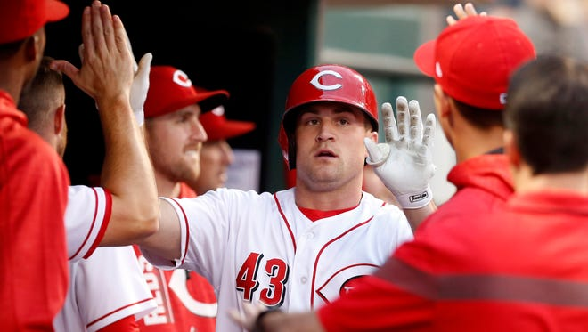 Cincinnati Reds right fielder Scott Schebler (43) is congratulated in the dugout.