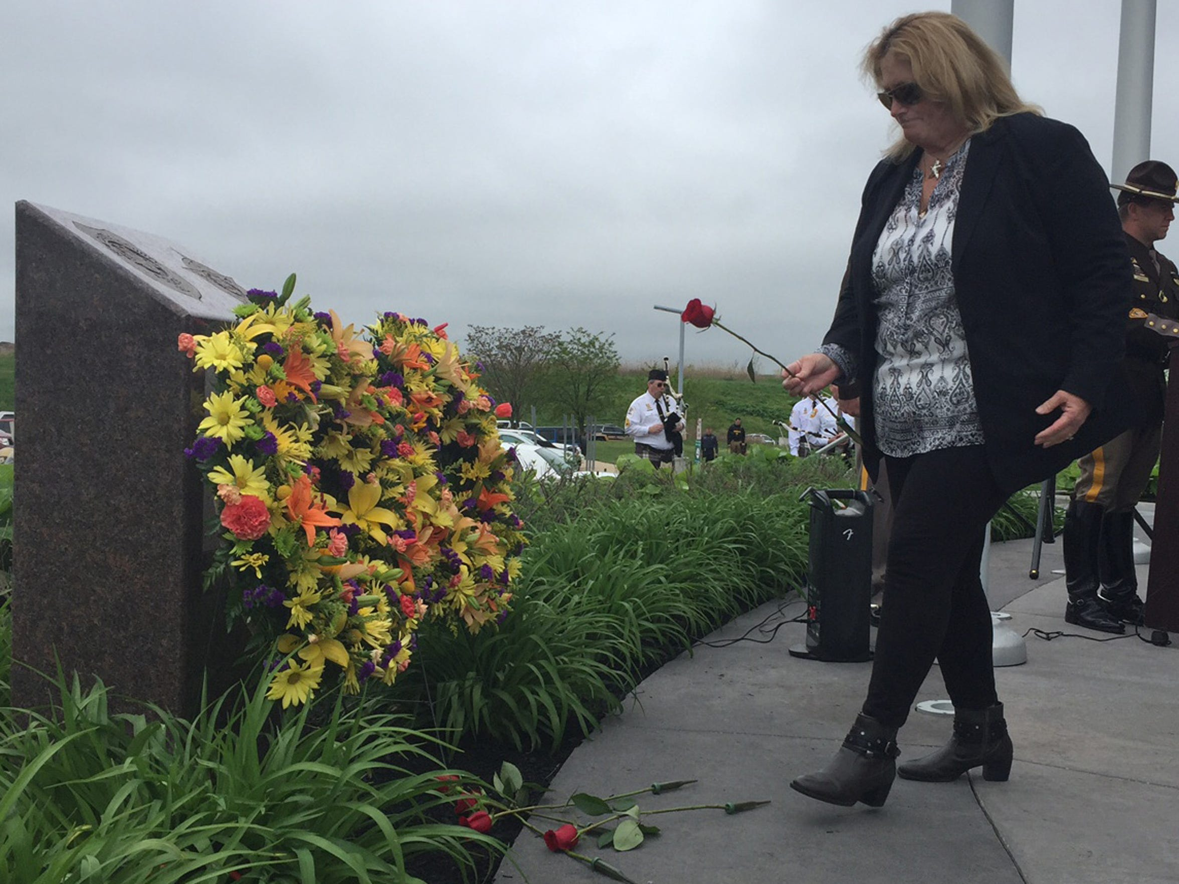 Sheila Sullivan carries a rose to present at a memorial in front of the Paul J. Sweeney Public Safety Building in Minquadale.  The rose is in honor of her father, Cpl. Ralph Dorris.  Eight other roses were laid at the memorial during the remembrance ceremony.