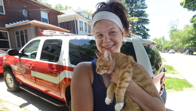 Tara Dennis, 21, poses for a photo with a cat after Erie firefighters rescued her after she got stuck while trying to rescue the cat that was stuck in a tree on June 15, 2014.