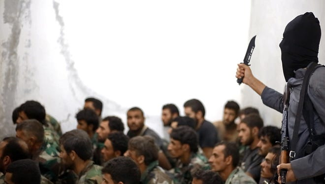 This undated image posted on Wednesday, Aug. 27, 2014, by the Raqqa Media Center of the Islamic State group shows a fighter armed with a knife and an automatic weapon next to captured Syrian army soldiers and officers.