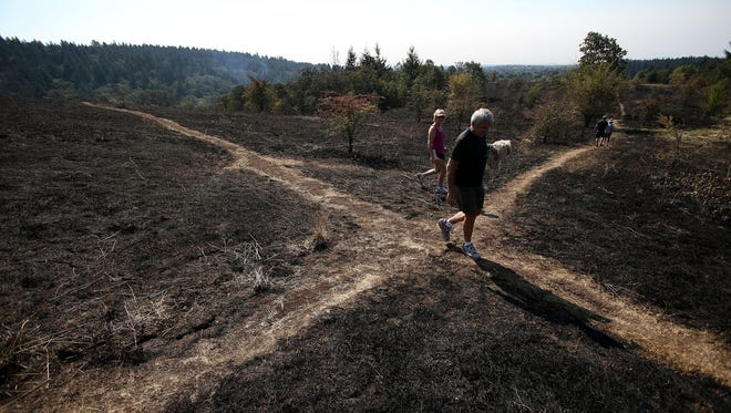 Karen Mueller and her husband, Fred, survey the damage from a 150-acre blaze in Corvallis in 2014. Wildfire season has begun; take steps to protect your home from wildfires.