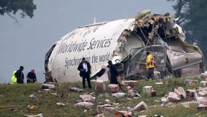 Investigators look through debris of a UPS A300 cargo plane after it crashed on approach at Birmingham-Shuttlesworth International Airport in Birmingham, Ala.