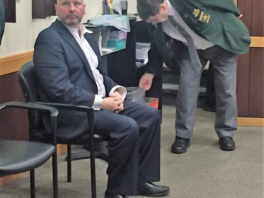 J. Patrick Buckley waits to be fingerprinted.
