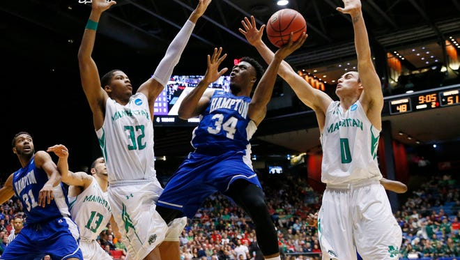 Hampton Pirates guard Reginald Johnson (34) goes up for a shot while defended by Manhattan Jaspers center Carlton Allen (32) and  forward Shane Richards (0) during the second half in the first round of the 2015 NCAA Tournament at UD Arena.