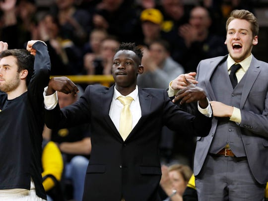 Iowa guard Peter Jok, center, celebrates on the bench with teammates Charlie Rose, left, and Riley Till during the second half of the team's NCAA college basketball game Ohio State, Saturday, Jan. 28, 2017, in Iowa City, Iowa. Iowa won 85-72. (AP Photo/Charlie Neibergall)