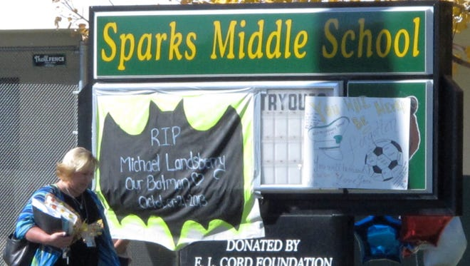Washoe County School Board President Barbara Clark walks Wednesday, Oct. 23, 2013, past a makeshift memorial in front of Sparks Middle School in Sparks, Nev.,  where math teacher Michael Landsberry was killed and two students wounded before a 12-year-old gunman killed himself.