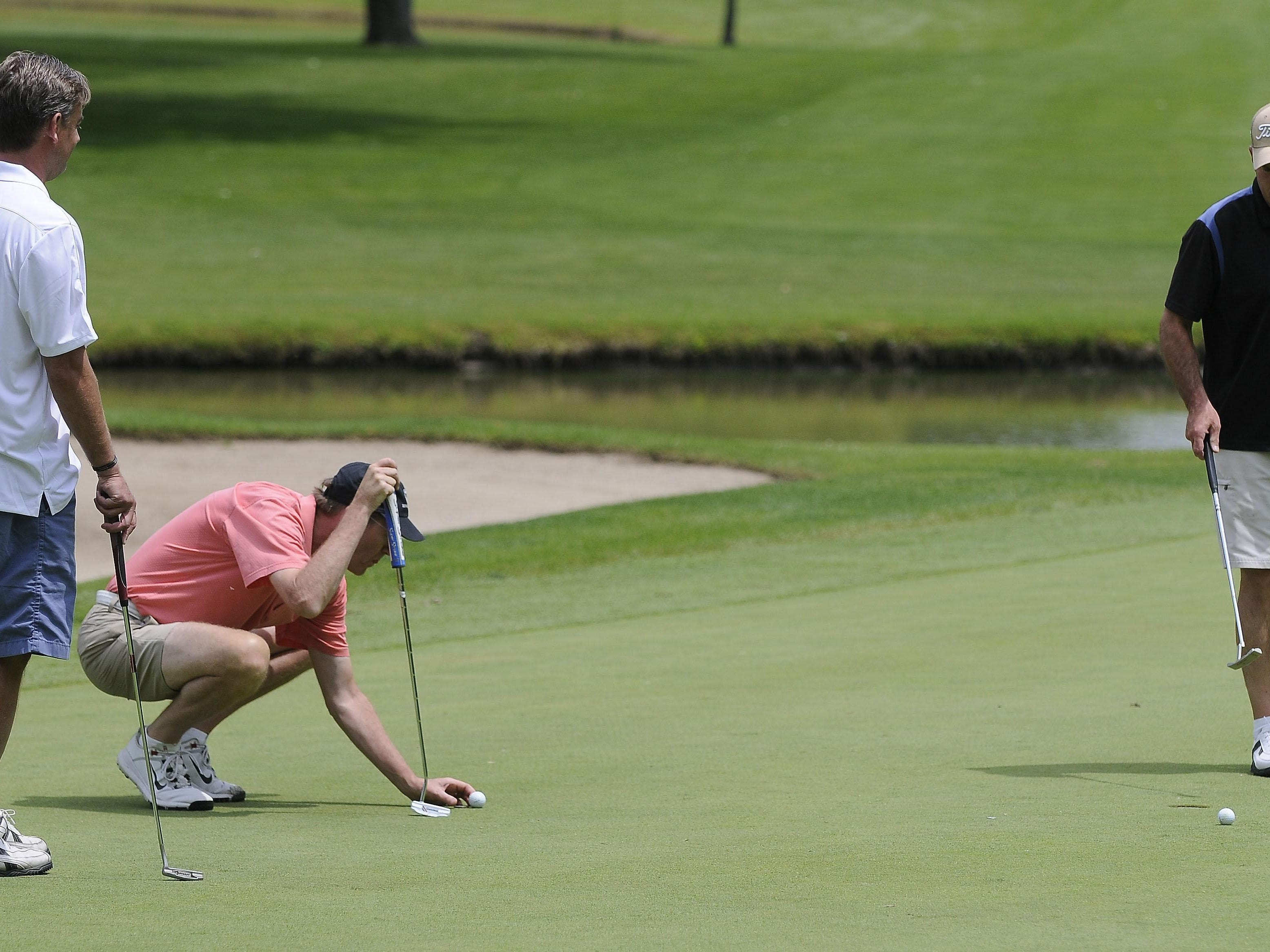 Mike Cansfield places his ball on the 18th hole as Rob McNeill, left, and Scot Smith look on during the Port Huron Elks 2015 Men's Invitational in Port Huron Township.