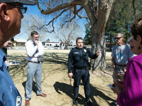 Las Cruces Police officer Rob A. Benavidez gets information at Klein Park on Wednesday, March 2, 2016, about a large bowtie that was a memorial for Miguel Silva which was recently stolen from the tree pictured in the background.